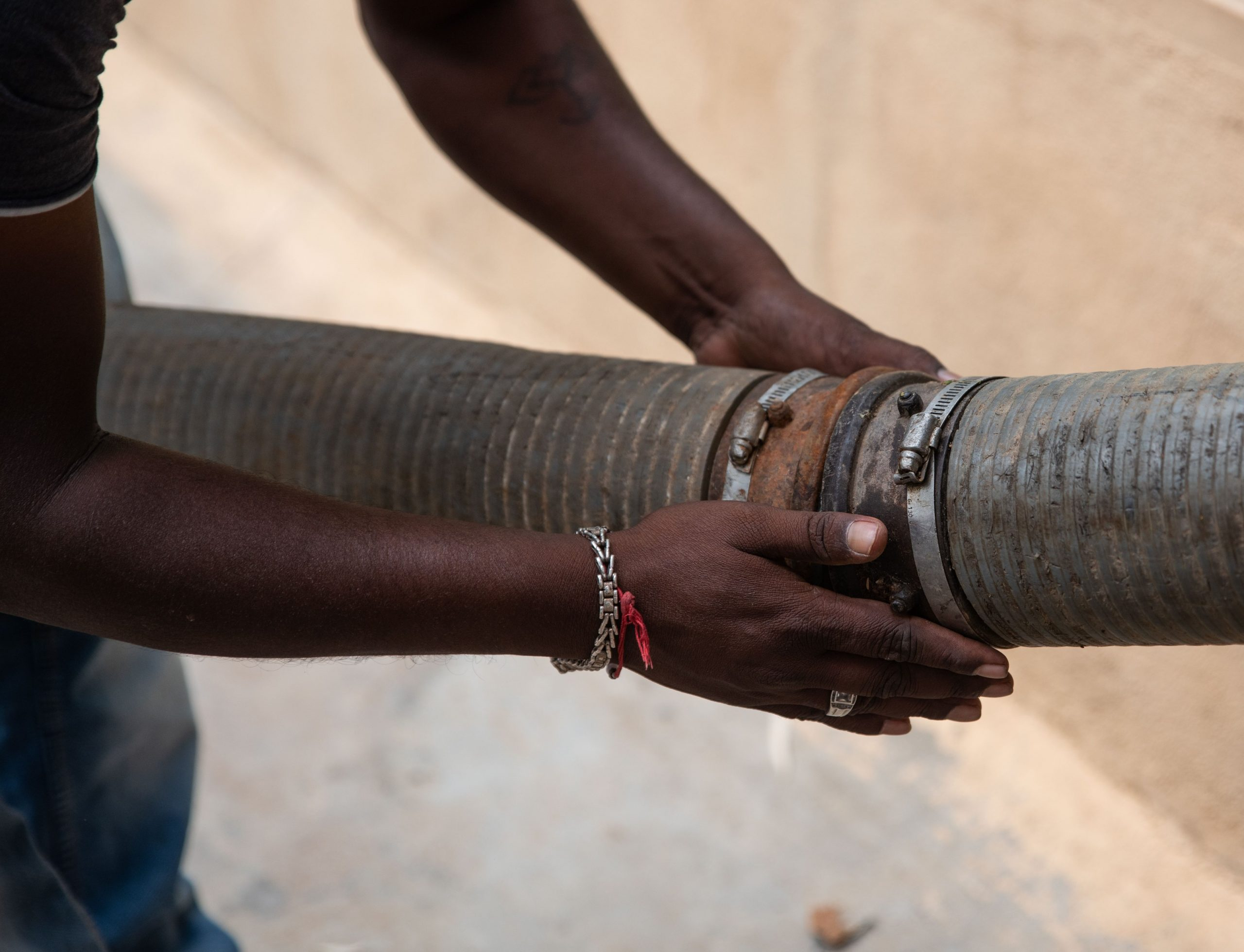 Men holding sewage pipe with bare hands_sanitation workers_epw