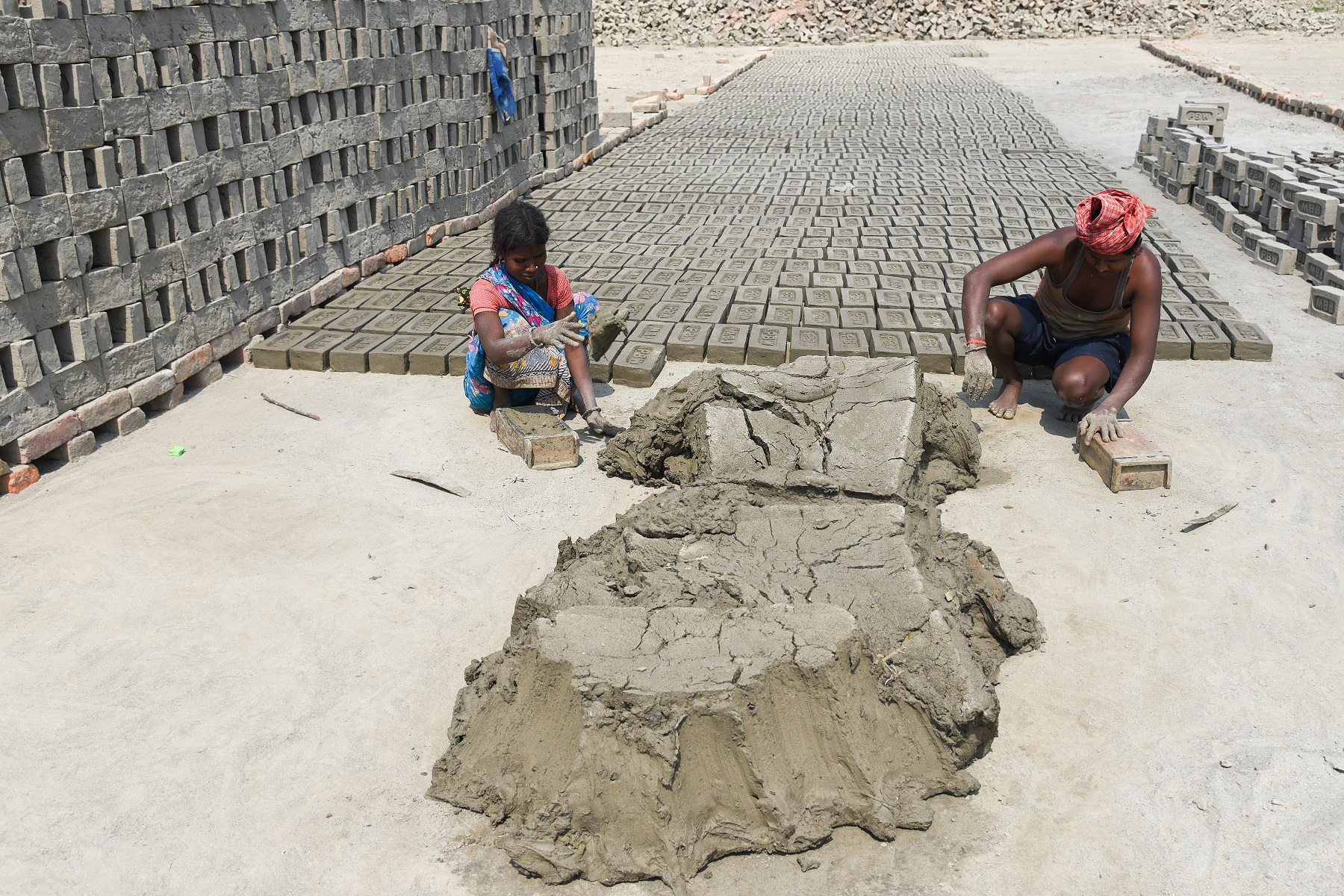 A young Indian girl and man making bricks out of clay at a brick kiln