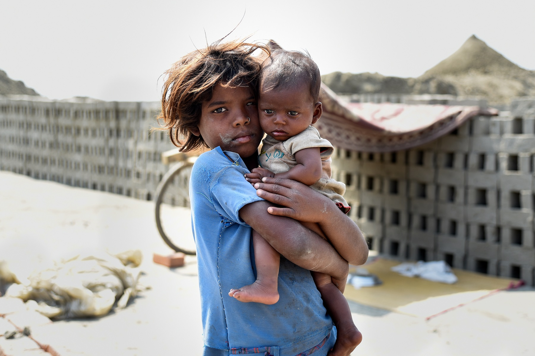 A young Indian girl with her baby sibling in her arms at a brick kiln