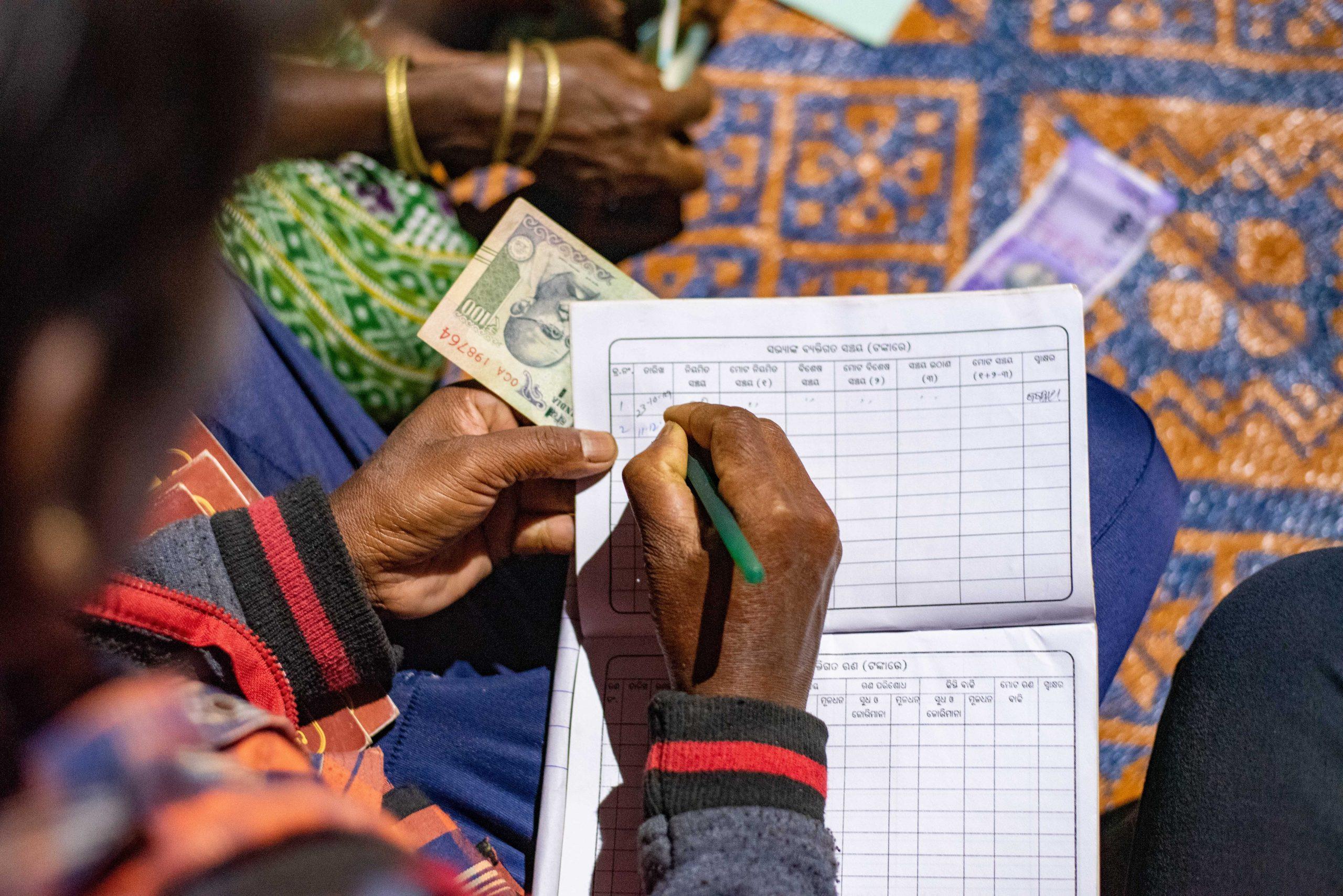 A fieldworker making an entry in a financial ledger