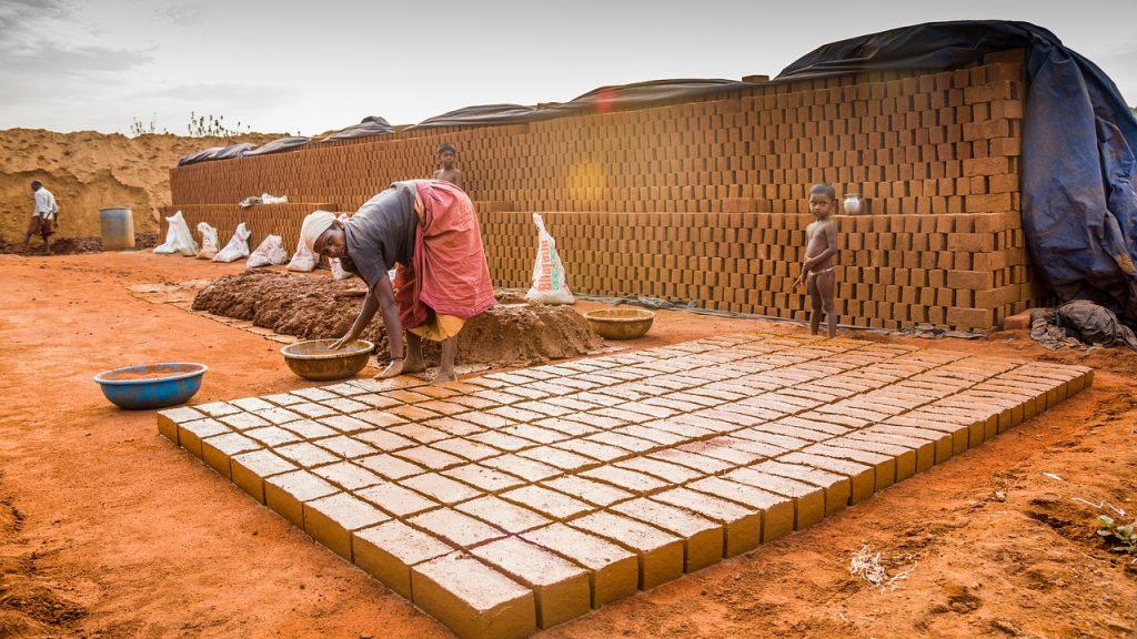 A woman in Tamil Nadu, India, laying bricks