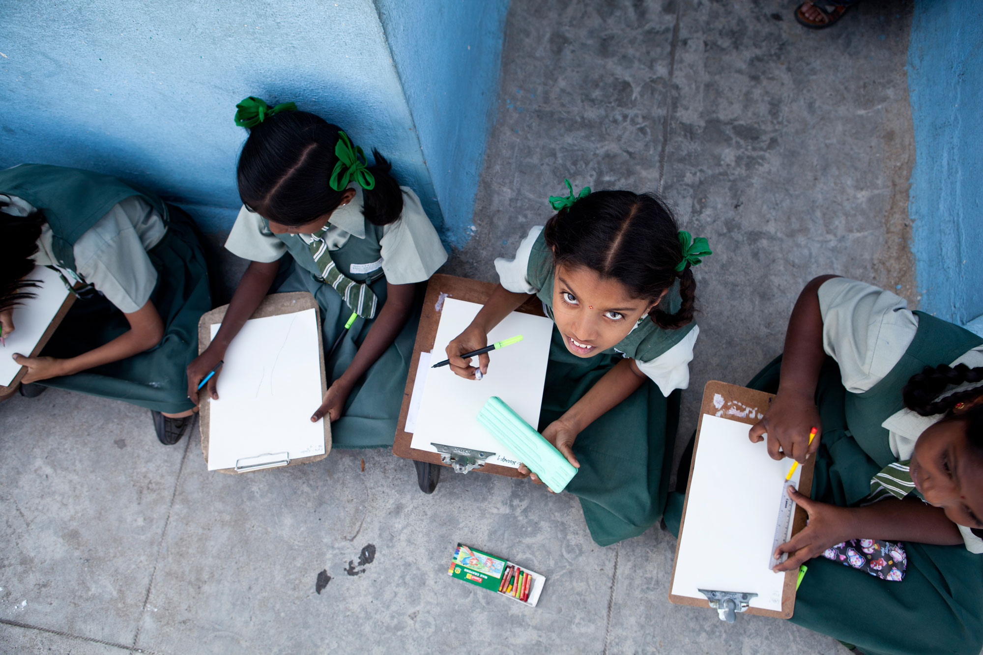 Arial shot of Indian school girls sitting on the floor doing homework_private schools