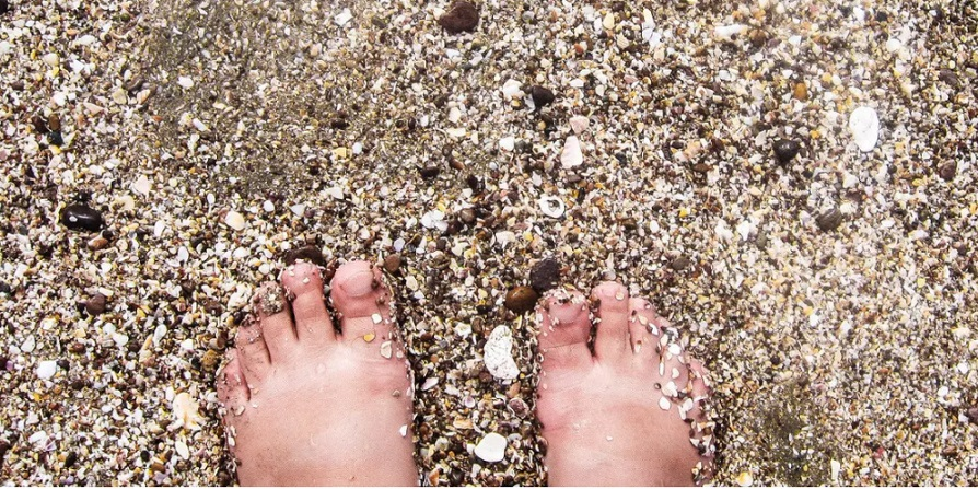 Photo by a blind photographer of feet on a beach in the sand
