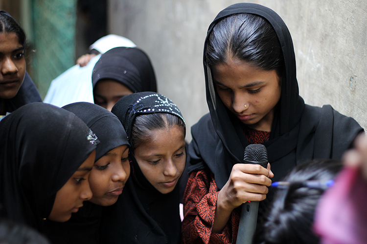 A group of young girls clustered around a mic