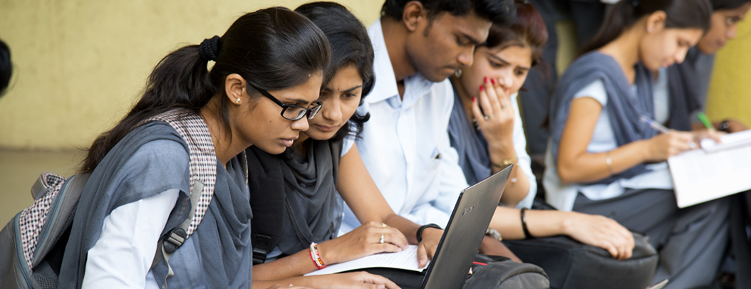 Indian students looking at a laptop