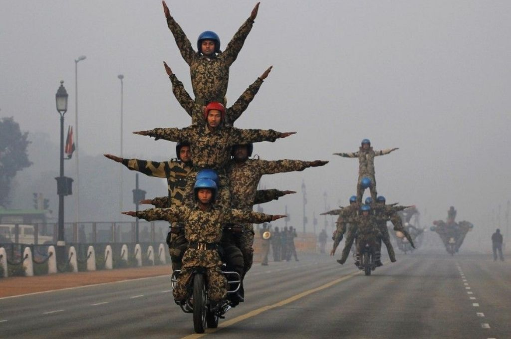 Soldiers performing a stunt on a bike
