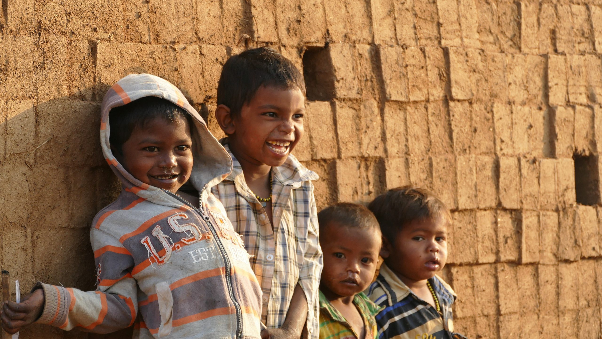 Young children laughing next to a brick kiln in Sonale, India