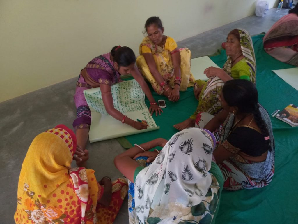 Kokila sitting and filling out a register among a group of women-domestic violence
