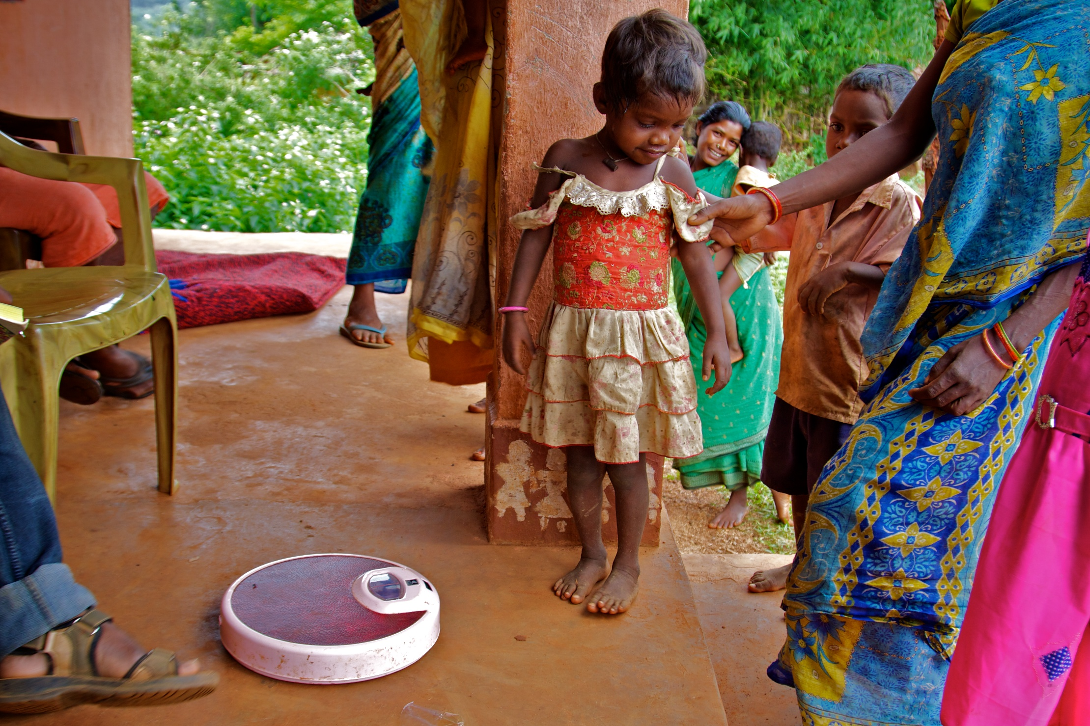 A young Indian girl child standing next to a weighing scale