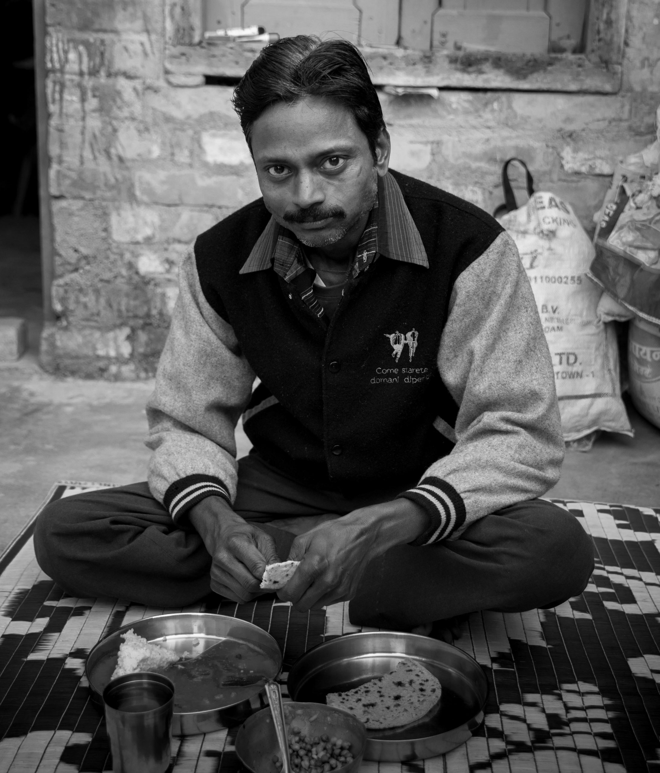 man sitting and eating on the ground