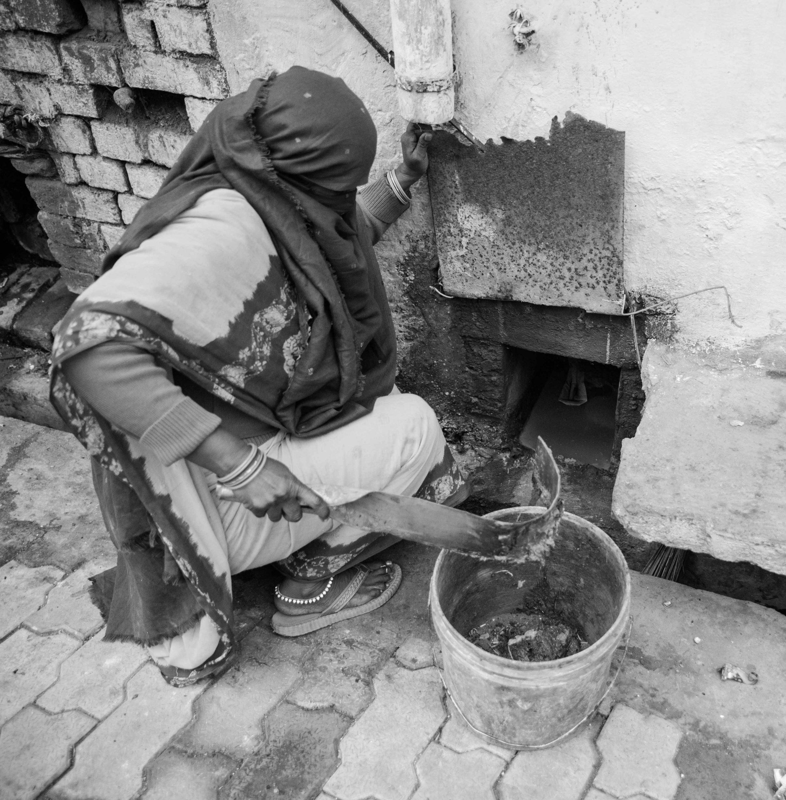 woman manually cleaning latrine