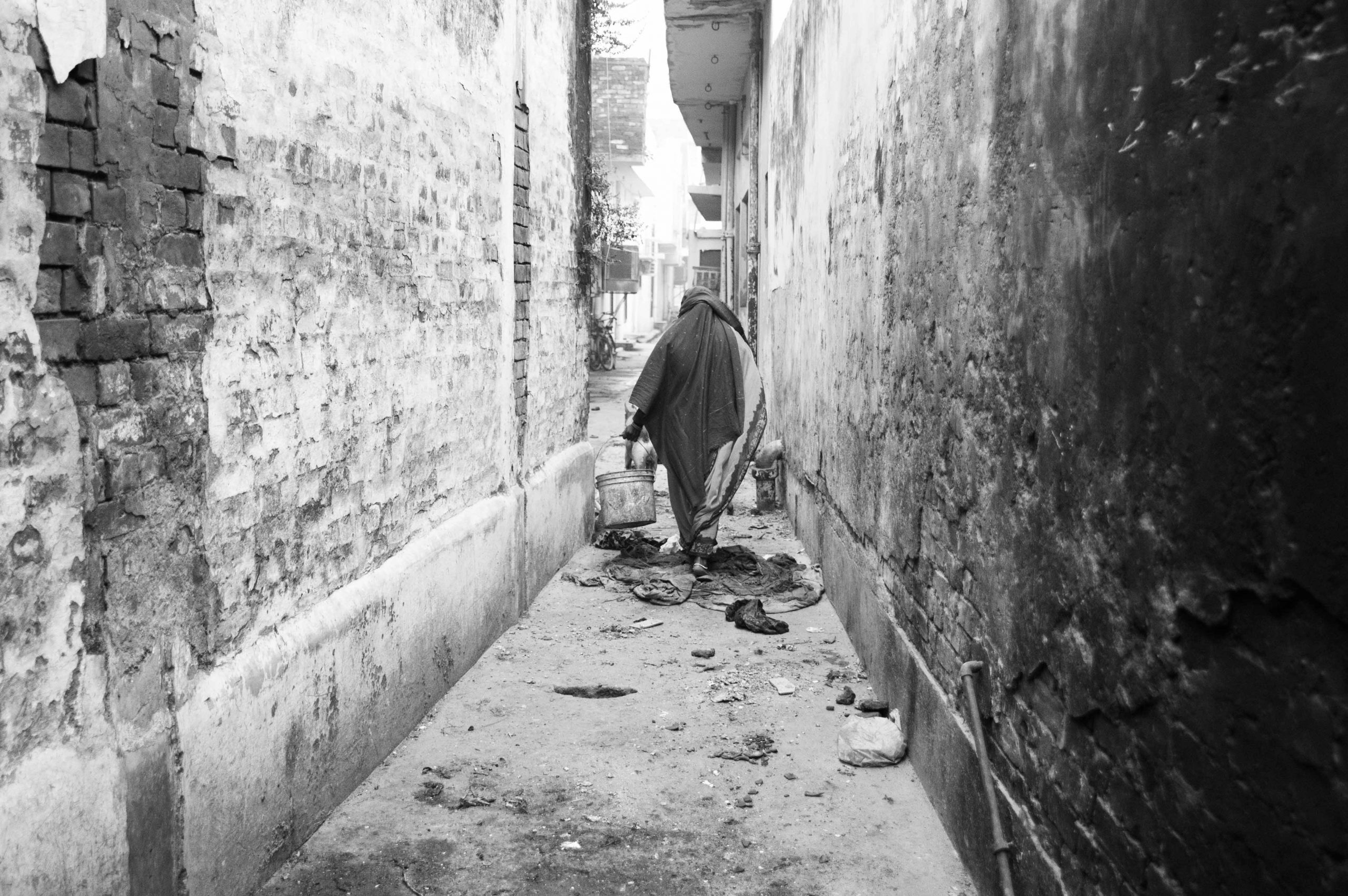 woman carrying buckets in alley
