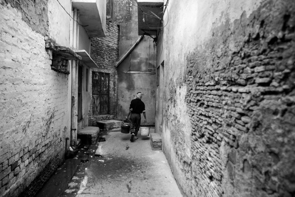 man carrying buckets of waste in an alley