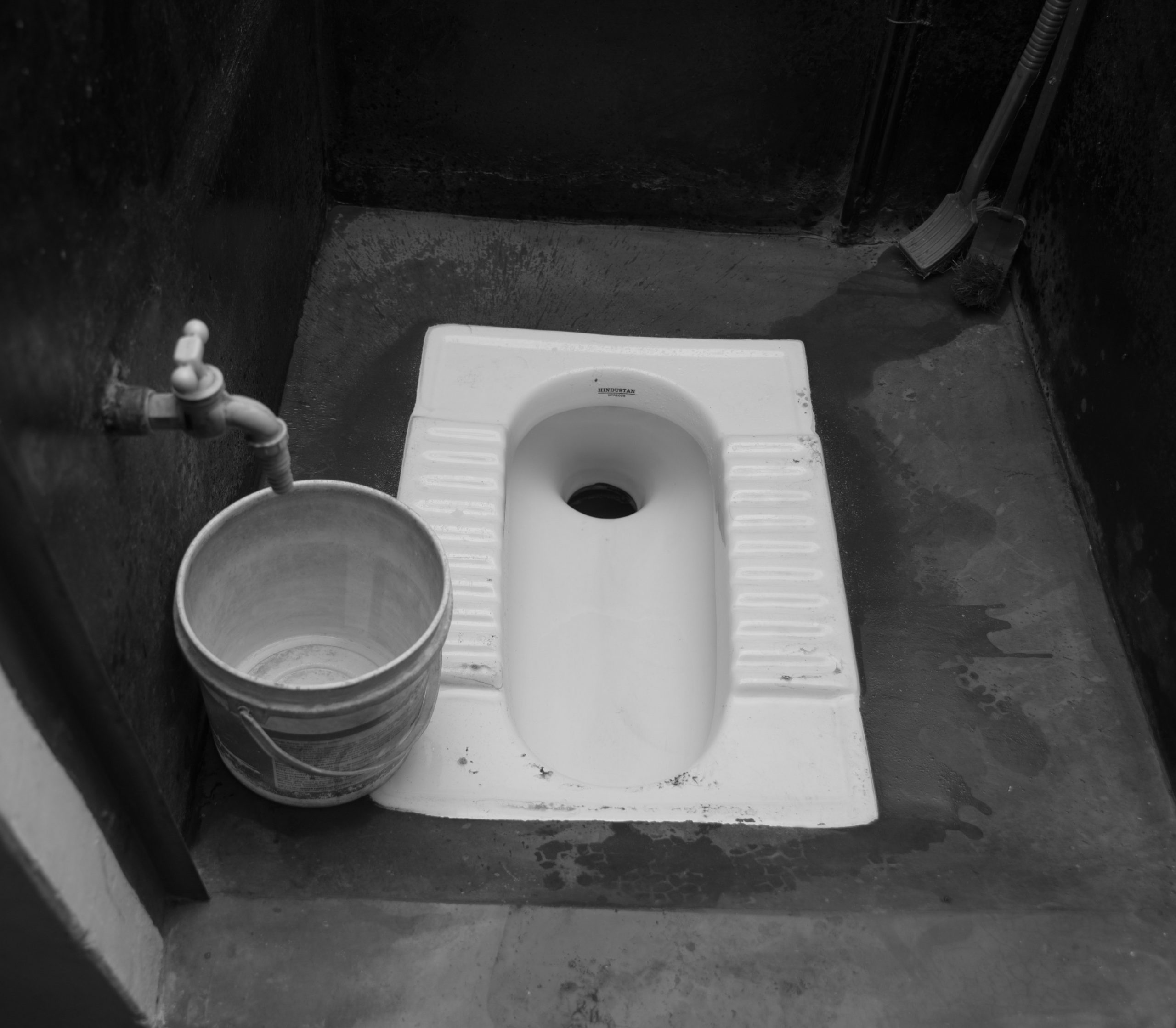 indian toilet in ground with bucket