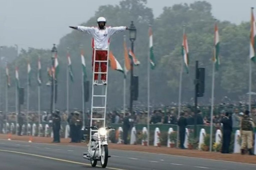 Man standing on ladder on a bike-Republic Day