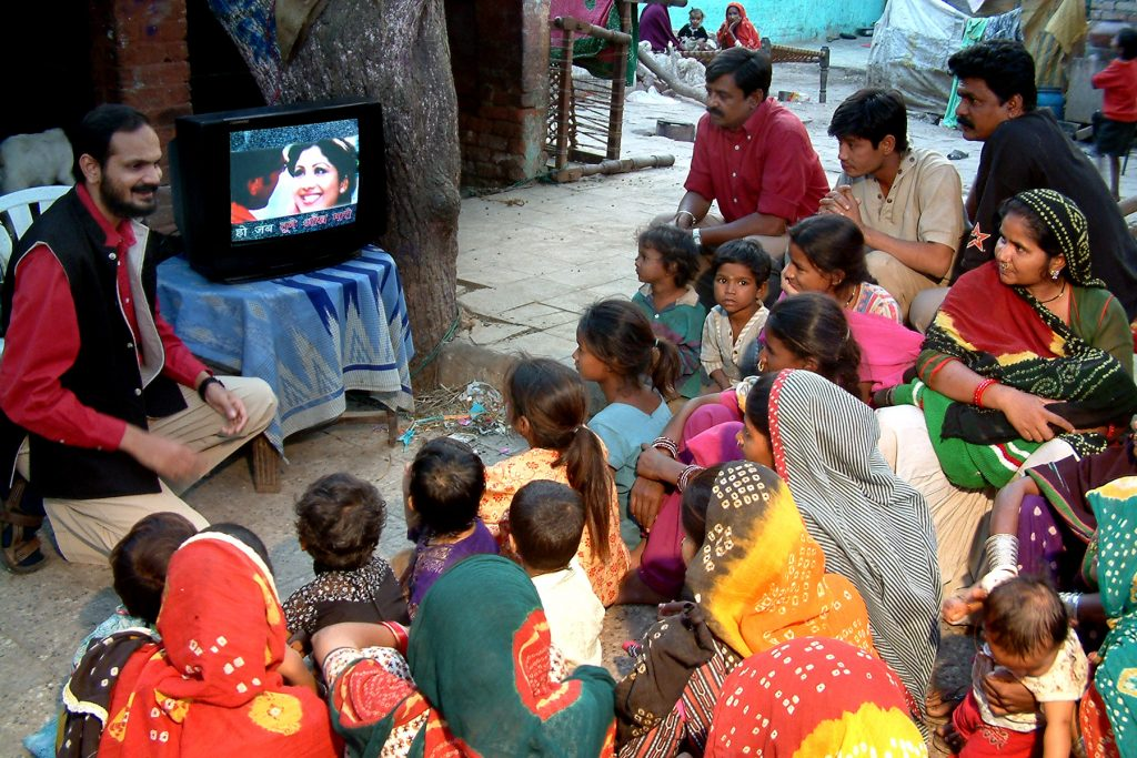 Indian people gathered around a television-entertainment education