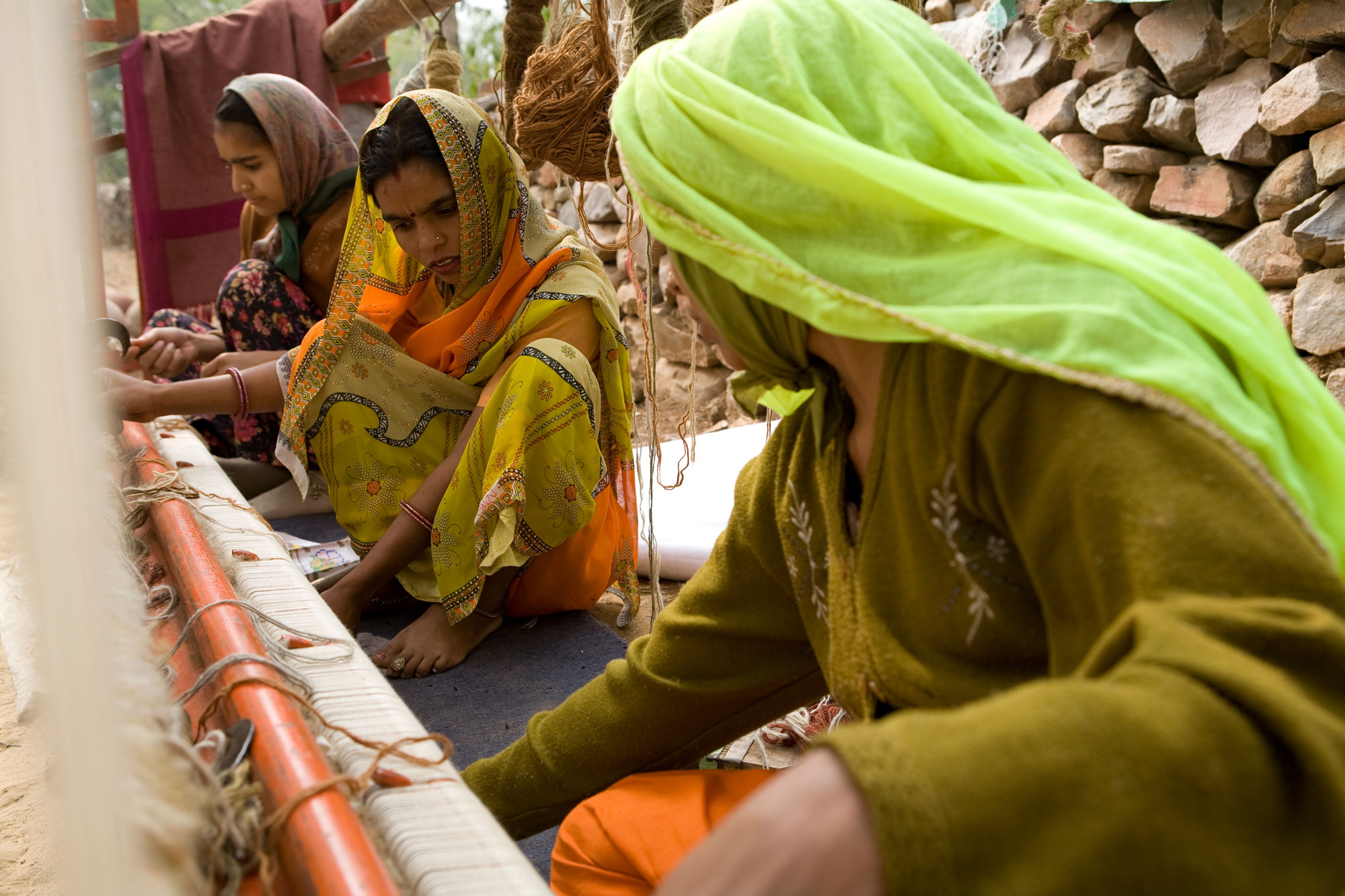 Indian women weaves carpet on a loom at Jaipur Rugs-collaboration