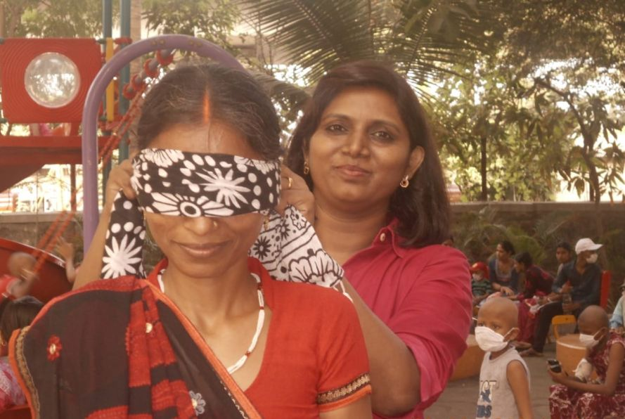 Madhubala blindfolding a mother as part of a game before covid-pediatric cancer