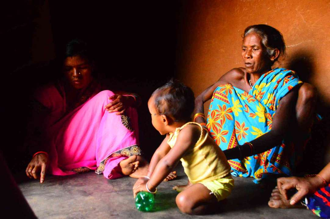 photo3-woman sitting with her family and child playing