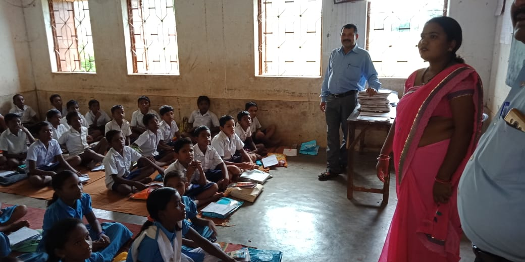 School children sitting on the floor with teachers standing-Panchayati Raj Institutions