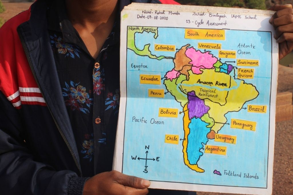 close up of Rahul Munda holding up a handrawn map of latin america-education