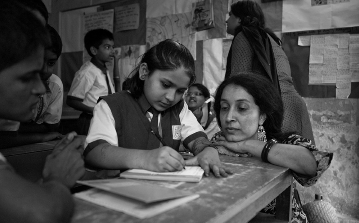 Shaheen Mistri sitting at a desk with a child