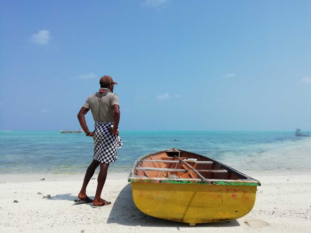 man standing by a small boat in the Lakshwadeep islands-fisheries