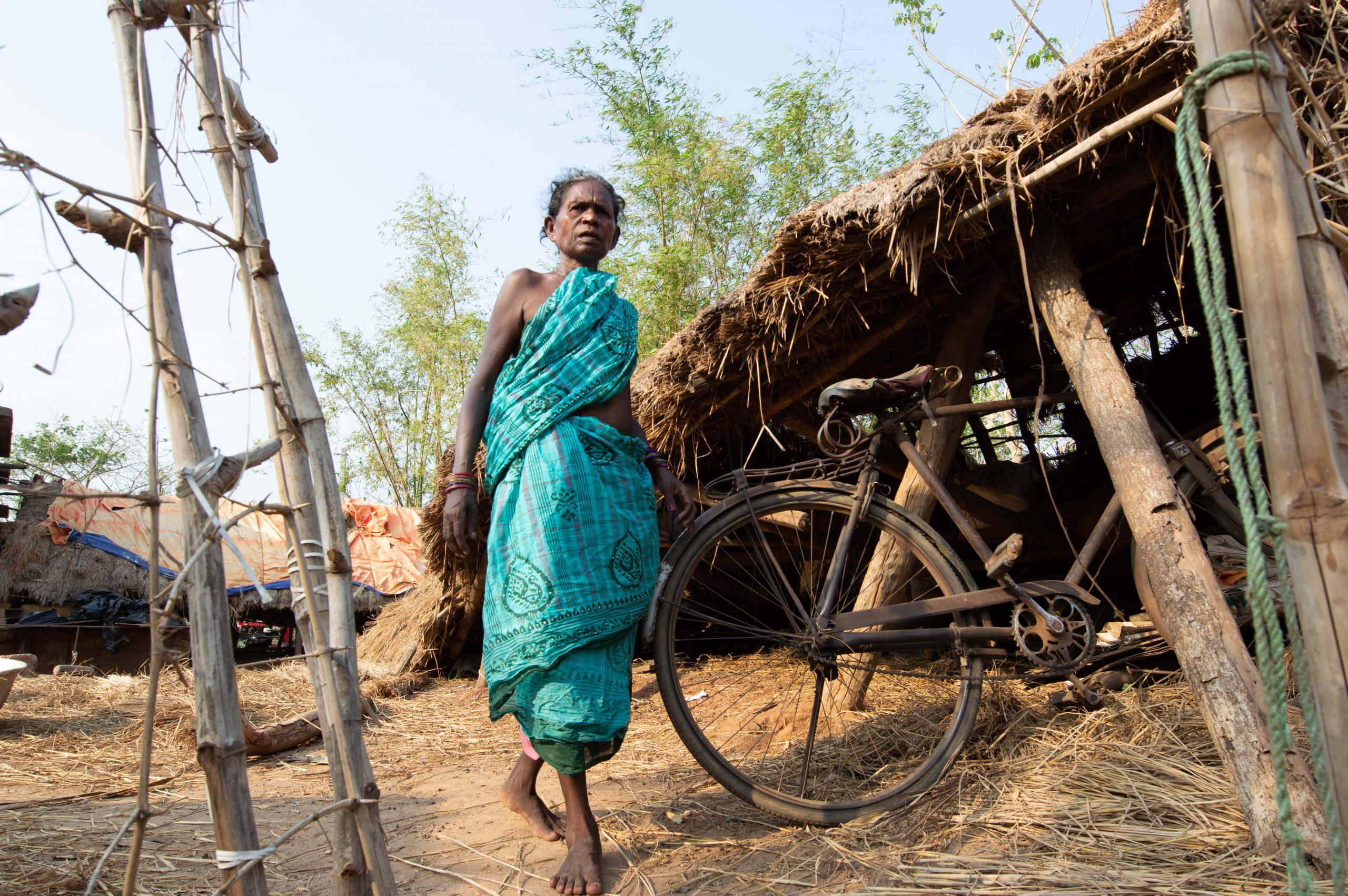 A woman walking through Sundarpur Mundasahi, Andharua, Odisha, after Cyclone Fani