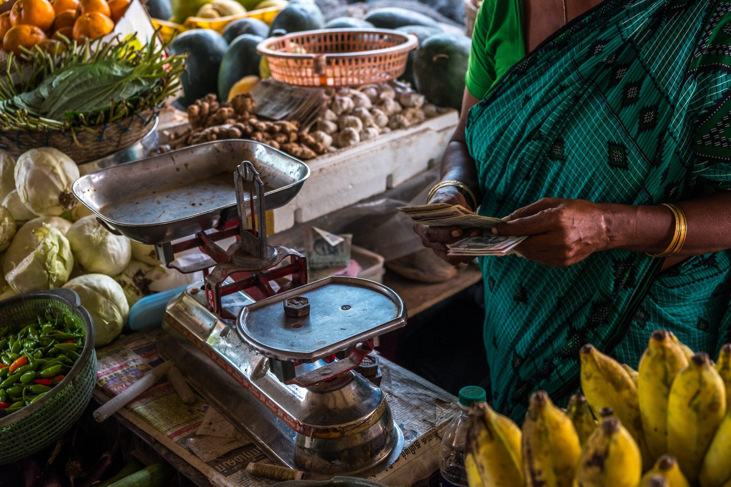 Woman vegetable vendor giving money-microenterprises