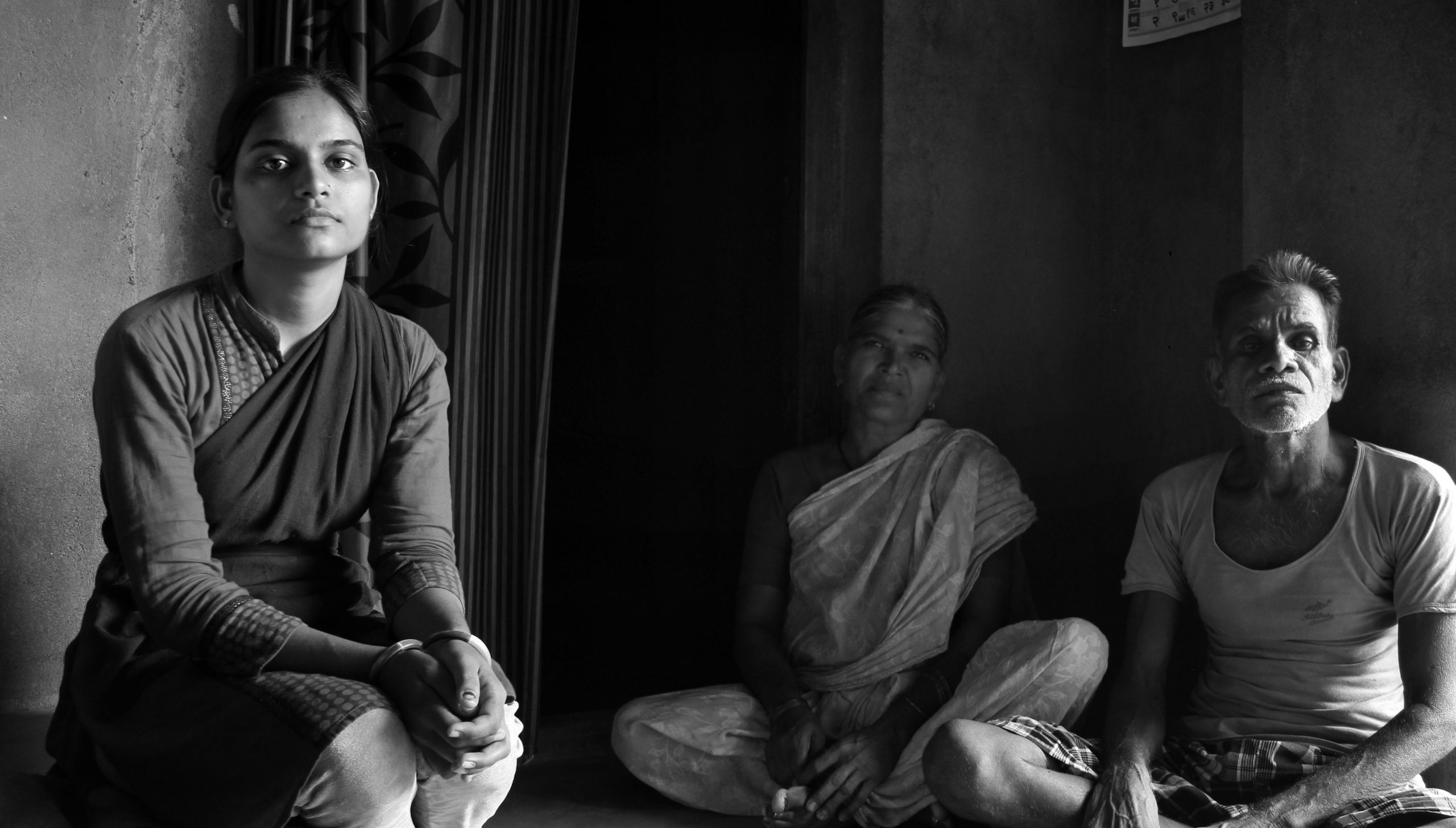 Young Indian girl seated alongside two older Indians-migration
