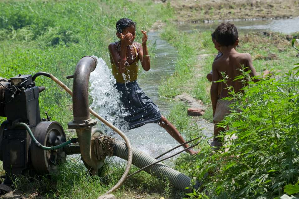 children playing at a borewell in indian farm_farmers