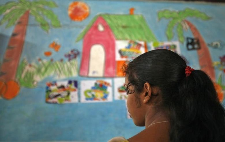 A girl looking at a classroom wall with paintings on it