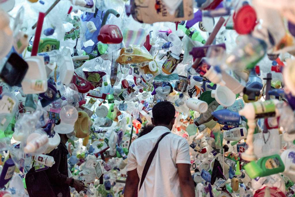 man walking through an exhibition surrounded by plastic-waste management