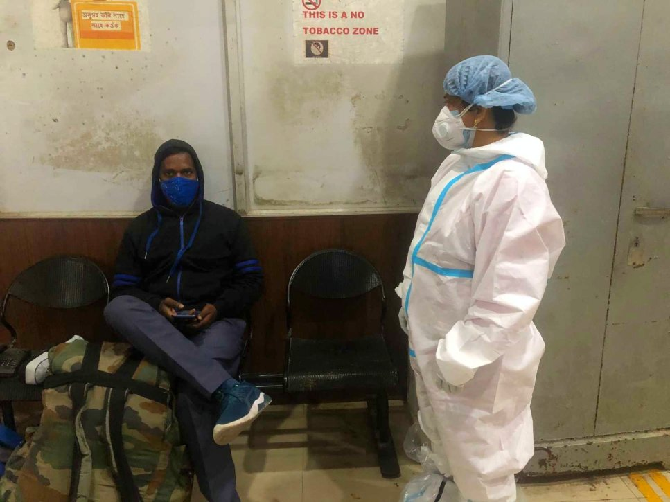 Monika Mandal wearing a PPE standing next to a seated masked man-ward worker