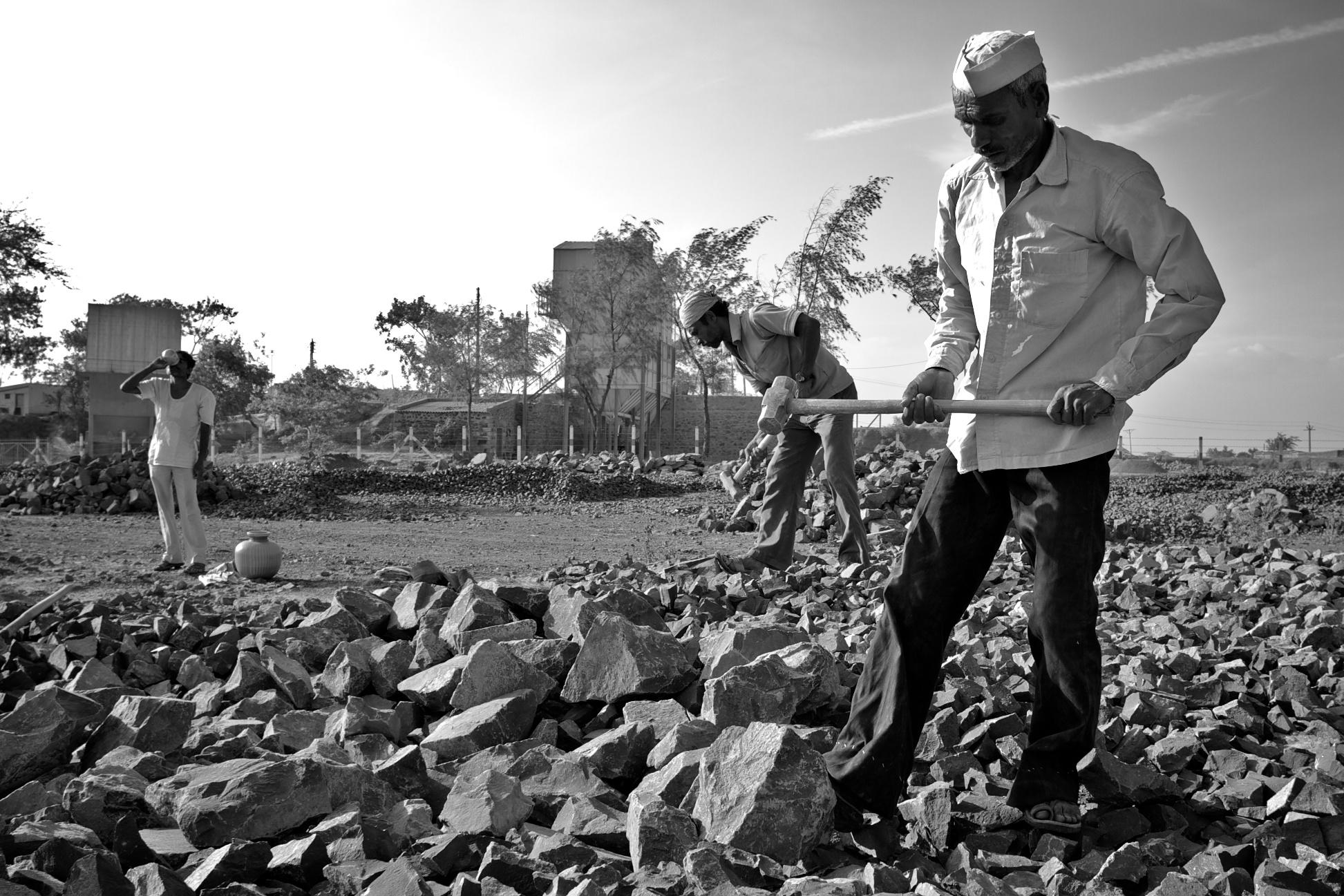 man breaking rocks in India-rural poverty