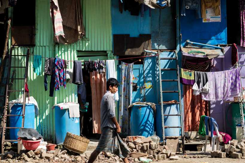 image of a young boy walking past a slum-urban development