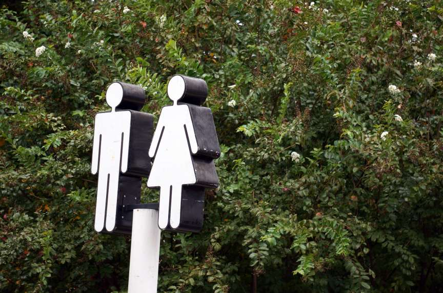 a restroom sign of a man and woman against a green background-gender