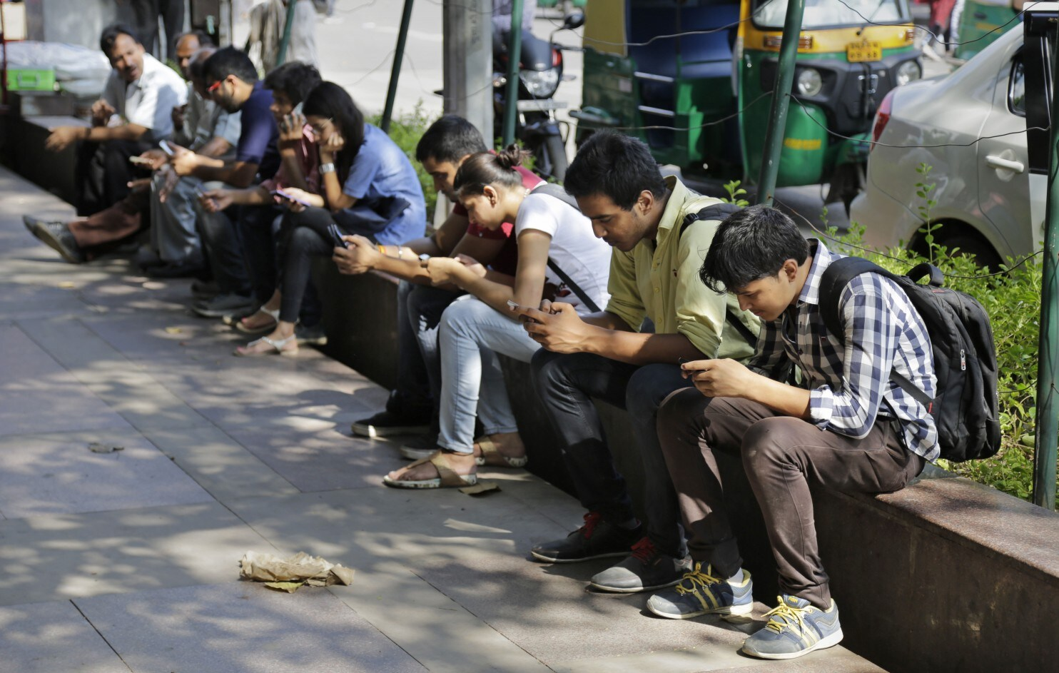 Young adults sitting on a bench on the road in India looking down at their smartphones
