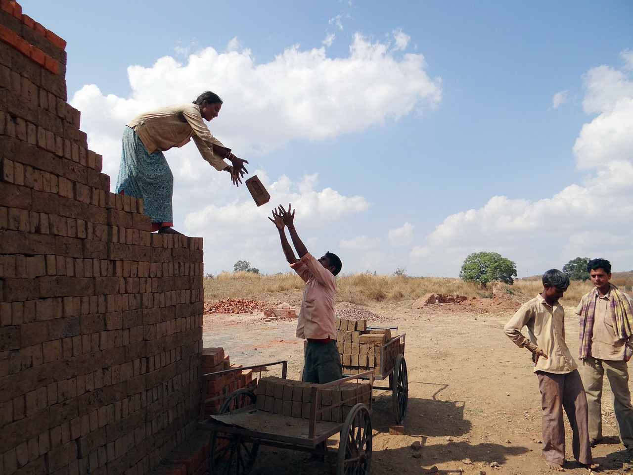 MNREGA workers passing bricks on a construction site
