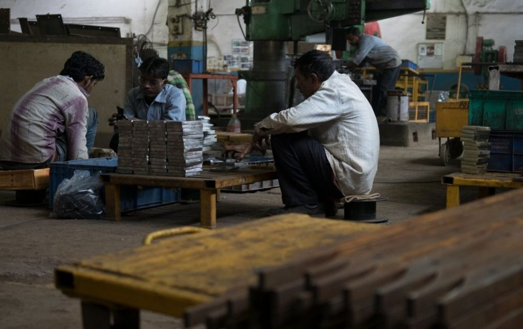 Three Indian factory workers at work