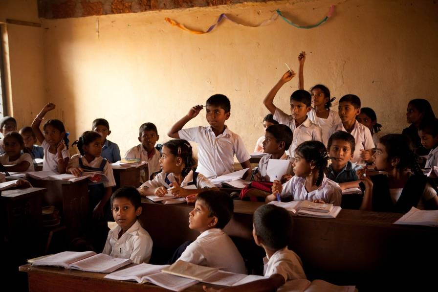Classroom with school uniform wearing children-development impact bonds