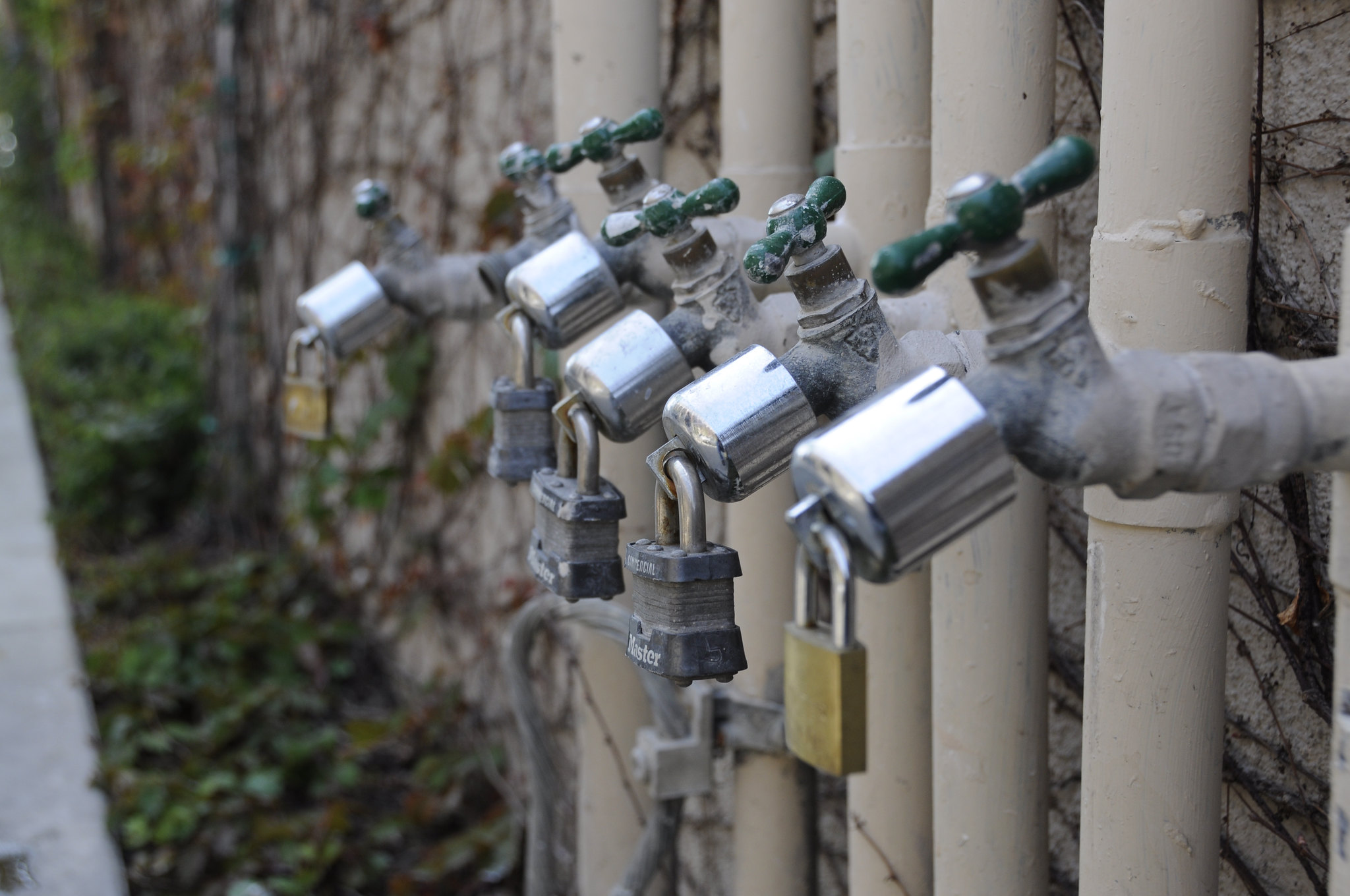 A row of water pipes with locks on theem_philanthropy needs to pay what it takes