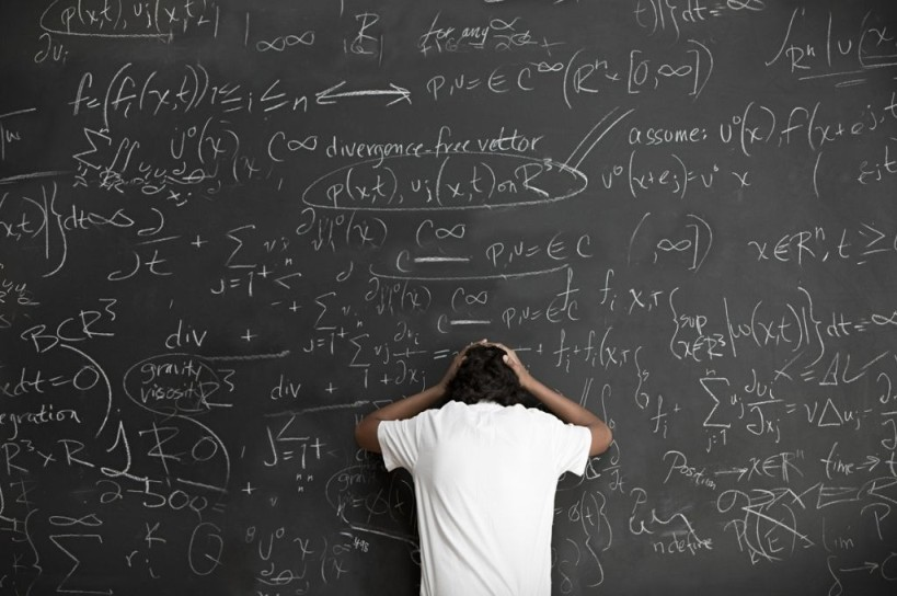Equations on blackboard with frustrated person trying to solve them-nonprofit