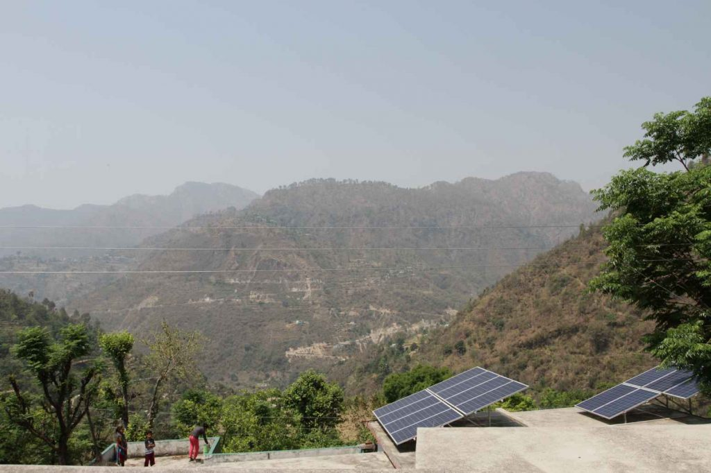 Power Farmers solar panels near Khadi overlooking hills with people standing near by- self-employment