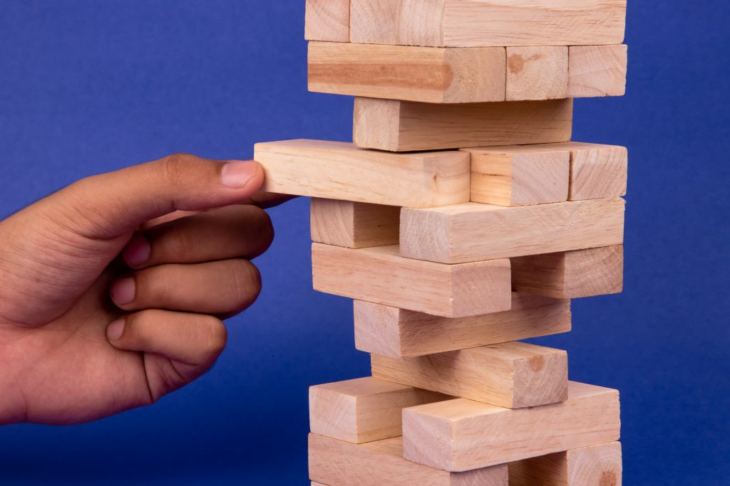 An inclined wooden block tower jenga game with hand-social stock exchange