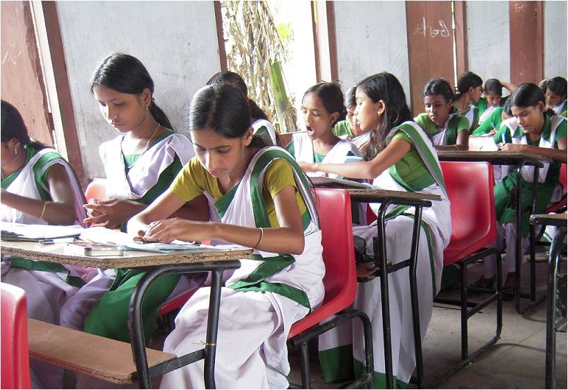 Students wearing uniforms sitting on benches next to each other writing-board exams