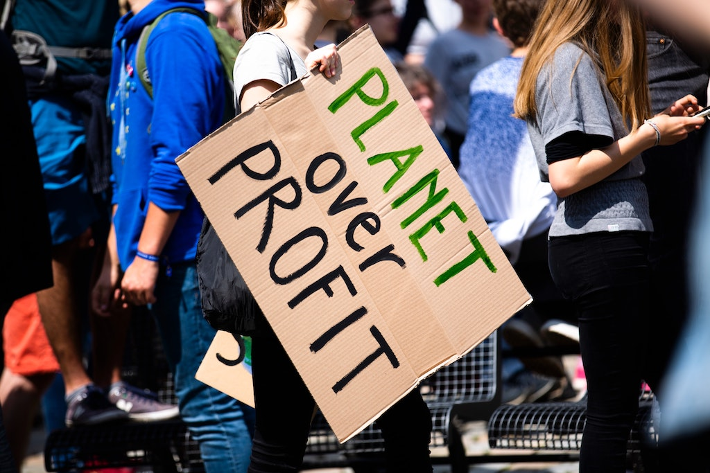 A person holding a brown placard saying planet over profit-climate change