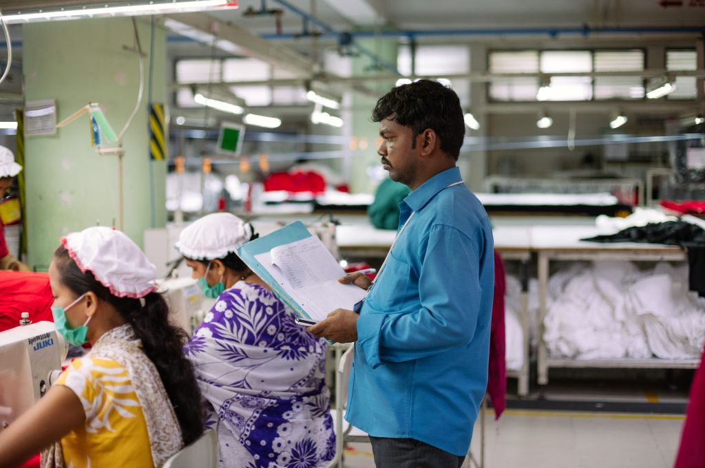 Male supervisor overseeing female garment workers-garment factories