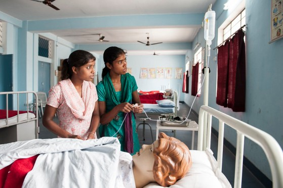 Two young girls in a hospital standing next to a hospital bed with a manequin-skill development programmes