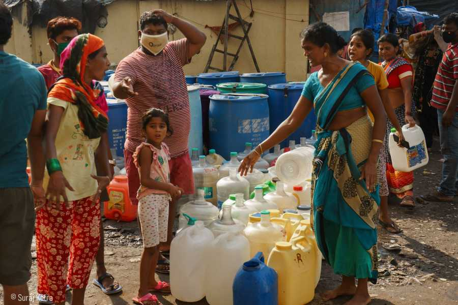 Image 10_People standing and talking next to stacked water containers-water for all-picture courtesy Suraj Katra
